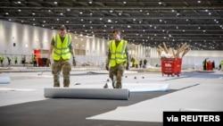 Tentara dari Resimen Royal Anglian membantu membangun Rumah Sakit NHS Nightingale yang baru untuk memerangi penyebaran virus corona (COVID-19), di London, Inggris, 27 Maret 2020.