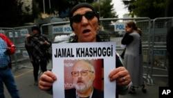 تصویر عضو انجمن حقوق بشر در استانبول که تصویر جمال خاشقجی را در دست دارد