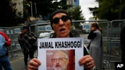 Một nhà hoạt động ở Istanbul mang chân dung ký giả Jamal Khashoggi.