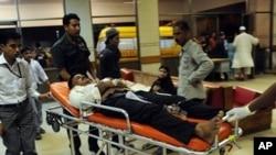 یهک له قوربانیانی توندوتیژیـیهکانی ناو شاری کهراچی گهیهندراوهته نهخۆشـخانه، یهکشهممه 17 ی دهی 2010