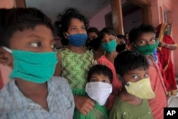 Evacuated children wearing masks as a precaution against the spread of coronavirus stand at a relief camp at Paradeep, on the Bay of Bengal coast in Orissa, India, Tuesday, May 19, 2020.