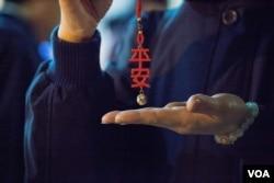 """台北第二殡仪馆内的慈济义工在现场分发""""平安""""挂饰。(美国之音记者方正拍摄)"""