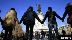 Orang-orang saling bergandengan tangan sebagai rasa solidaritas pasca serangan maut di dekat gedung konser Bataclan, di Paris (15/11). Grup band AS 'Eagles of Death Metal' sedang manggung di gedung ini ketika serangan maut terjadi hari Jumat malam (13/11).