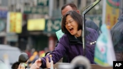 Taiwan's opposition Democratic Progressive Party, DPP, presidential candidate Tsai Ing-wen greets supporters from the back of a truck as she parades through the streets of New Taipei City, Taiwan, Friday, Jan. 15, 2016.