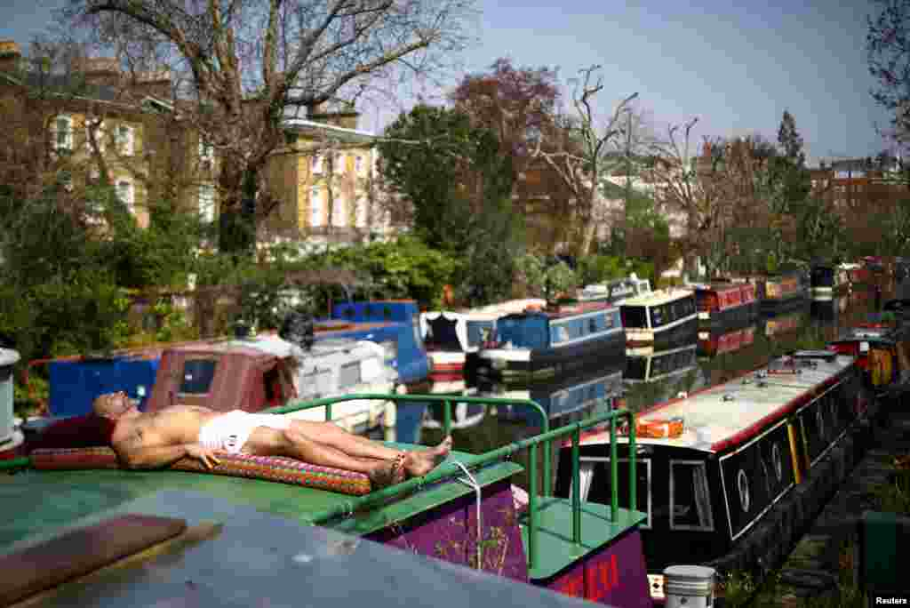 A man enjoys the sun on top of a canal boat in Little Venice as the spread of the coronavirus disease (COVID-19) continues, in London, Britain.