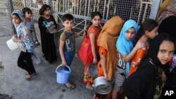 FILE - Iraqi children, most of them internally displaced persons, wait in line for free food being distributed at a mosque in Baghdad, Iraq, June 23, 2015.