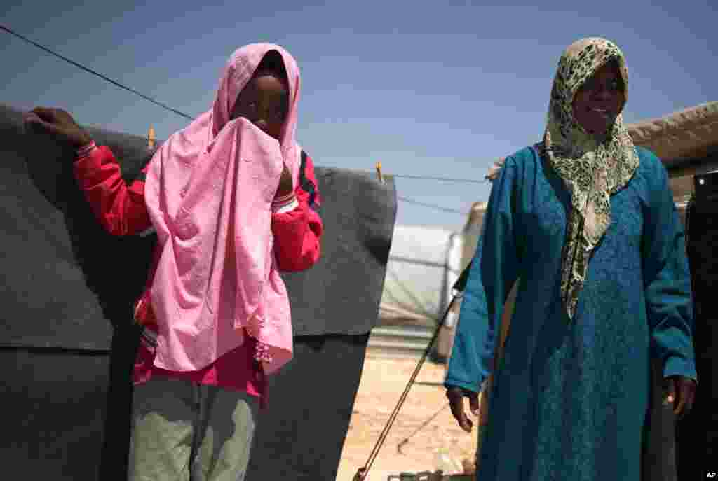 Syrian refugee Omm Mohammed, 33, right, and her daughter, stand in front of their family tent at Zaatari Syrian refugee camp, in Mafraq, Jordan, August 28, 2013.