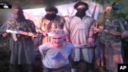 In this still image from video published on the Internet on Sept. 24, 2014, by a group calling itself Jund al-Khilafah, or Soldiers of the Caliphate, members of the group stand behind French mountaineer Herve Gourdel just before beheading him.