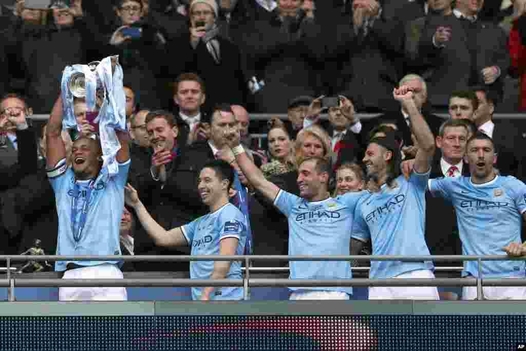 Vincent Kompanty na Manchester City rike da kofin yayin da sauran 'yan wasa ke nuna murnarsu.