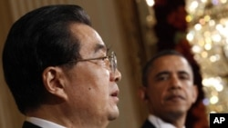 U.S. President Barack Obama looks on as Chinese President Hu Jintao speaks during a joint news conference in the East Room of the White House in Washington, 19 Jan 2011