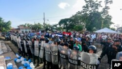 FILE - Police form a cordon outside a church where a Mass is celebrated for the freedom of political prisoners, in Masaya, Nicaragua, Aug. 28, 2019.