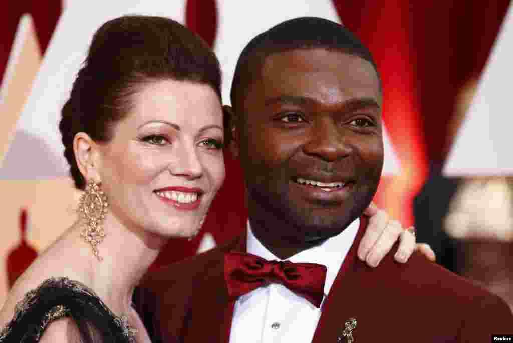 """Actor David Oyelowo, protagonista de """"Selma"""" e a mulher Jessica. Ele exibindo um pin """"Parem o Ébola"""""""
