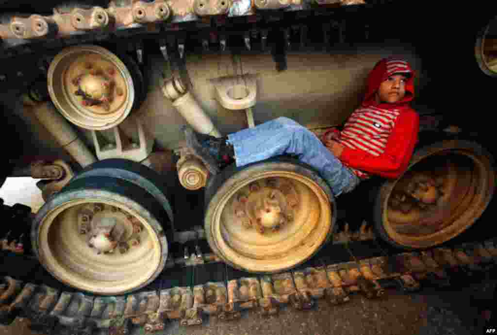 A boy sits inside the tracks of an army tank in Tahrir Square, Cairo on Friday. (Reuters/Suhaib Salem)