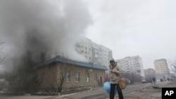 ស្រ្តីម្នាក់ដើរកាត់ផ្ទះឆេះមួយក្នុងតំបន់ Mariupol ក្នុងប្រទេសអ៊ុយក្រែន កាលពីថ្ងៃសៅរ៍ ទី២៤ ខែមករា ឆ្នាំ២០១៥។