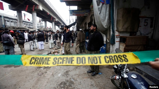 Police investigators cordon off a site of a bomb attack in a market selling mobile phones at Hashtnagri bazaar in Peshawar, February 21, 2013.