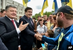 FILE - Seen during better times, Ukrainian President Petro Poroshenko, left, and then newly appointed Odesa region governor Mikheil Saakashvili, second left, shake hands with local residents, in Odesa, Ukraine, May 30, 2015.