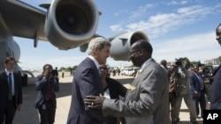 Janubiy Sudan Tashqi ishlar vaziri Barnaba Marial Benjamin Amerika bosh diplomati Jon Kerrini kutib oldi. 2-may, Juba, Janubiy Sudan.