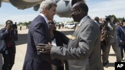 South Sudanese Foreign Minister Barnaba Marial Benjamin, right, welcomes US Secretary of State John Kerry upon his arrival at Juba International Airport, South Sudan, Friday May 2, 2014. Kerry, landing in the capital Juba on Friday, has threatened U.S.sanctions against South Sudanese leaders.