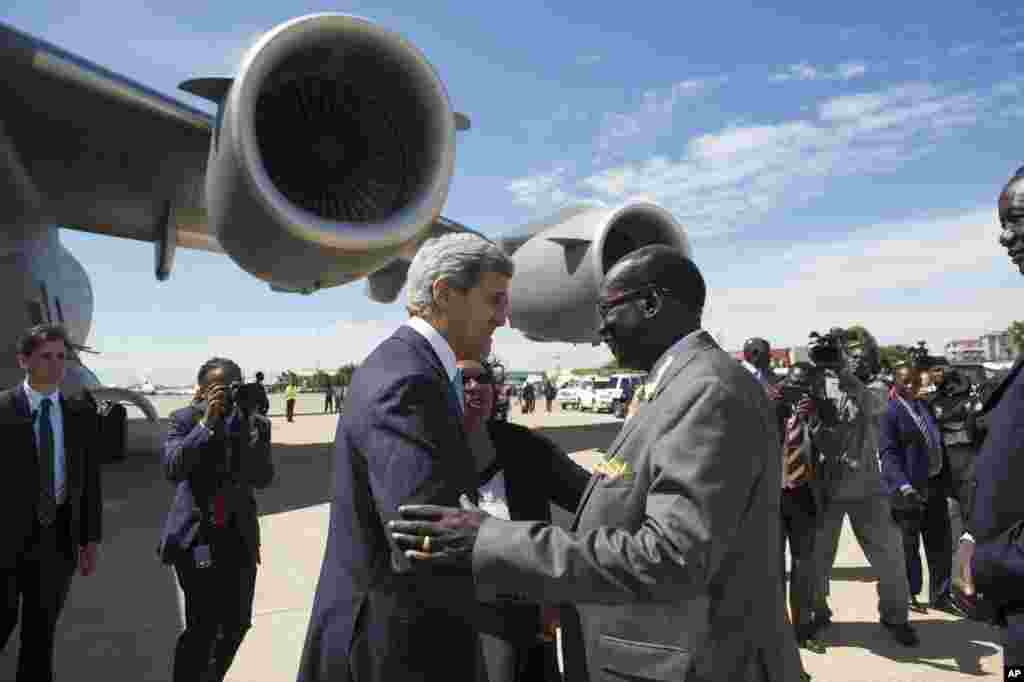 South Sudanese Foreign Minister Barnaba Marial Benjamin welcomes U.S. Secretary of State John Kerry upon his arrival at Juba International Airport, South Sudan, May 2, 2014.