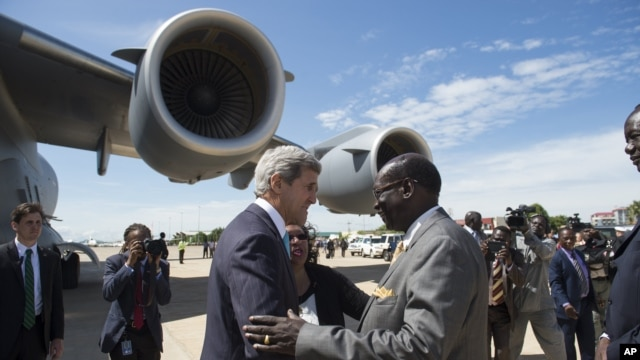 South Sudanese Foreign Minister Barnaba Marial Benjamin, right, welcomes US Secretary of State John Kerry at Juba International Airport, Friday May 2, 2014. On Tuesday, the United States imposed sanctions on two South Sudanese military leaders, one from each side of the conflict.