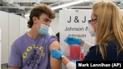 In this July 30, 2021 file photo, Bradley Sharp, of Saratoga, N.Y., gets the Johnson & Johnson vaccine from registered nurse Stephanie Wagner, in New York. Sharp needs the vaccination because it is required by his college. Hundreds of college campuses across the country have told students that they must be fully vaccinated against COVID-19 before classes begin in a few weeks. (AP Photo/Mark Lennihan, File)