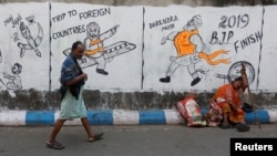 FILE - A man walks past a woman who sits by a wall with graffiti that mocks Indian politicians ahead of the general election in Kolkata, India, Apr. 1, 2019.