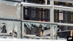 FILE - An arrivals and departure board is seen behind blown out windows at Zaventem Airport in Brussels, Belgium, March 23, 2016. The European Union on Wednesday, Nov. 16, 2016 unveiled plans for a new system of security checks on travelers permitted to enter Europe without visas in an effort to crack down on extremists.