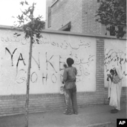 "A resident of Tehran washes ""Yankee Go Home"" graffiti from a wall in the capital city of Iran, Aug. 21, 1953. The new Premier Gen. Fazlollah Zahedi requested the cleanup after the coup d'etat, which restored the Shah of Iran in power."
