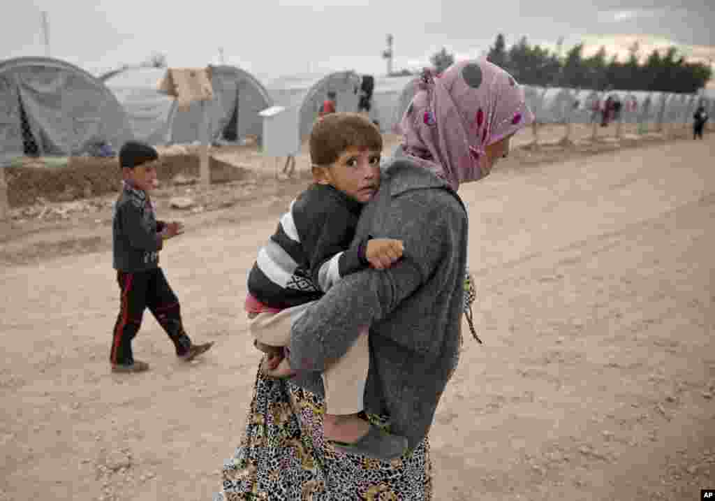 A Syrian Kurdish refugee from Kobani carries a young child, at a refugee camp in Suruc, Turkey, Oct. 23, 2014.