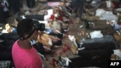 埃及鎮壓行動傷亡慘重﹐一名救援人員在停屍間觀看排列的屍體。