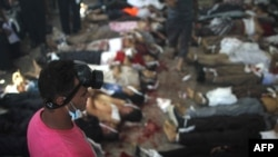 FILE - A man looks at bodies laid out in a make shift morgue after Egyptian armjy and police forces stormed two huge protest camps at the Rabaa al-Adawiya and Al-Nahda squares, killing hundreds of supporters of ousted president Mohamed Morsi, Cairo, August 14, 2013.