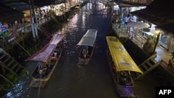 This picture taken on March 28, 2015 shows boats carrying visitors along the Amphawa canal, a small tributary of the Mae Khlong River, in Samut Songkhram province some 80 kilometers west of Bangkok.