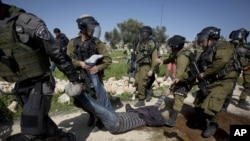 Israeli security forces detain a Palestinian protester during a demonstration marking the 10th anniversary of their campaign against Israel's separation barrier in the West Bank village of Bilin near Ramallah, Feb. 27, 2015.