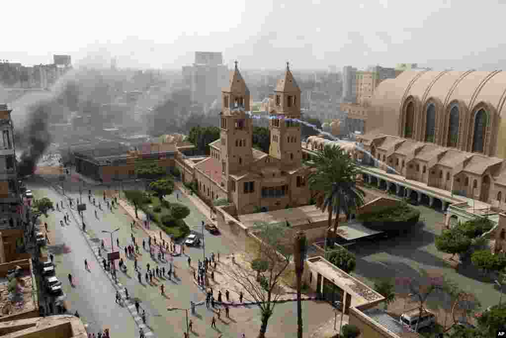 Egyptian riot police fire tear gas into the compound of the Coptic Orthodox Cathedral after the funeral of four Christians killed in sectarian clashes near Cairo, April 7, 2013.
