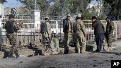 Afghan policemen investigate at the site of a suicide bomb attack in Nangarhar province, March 5, 2012