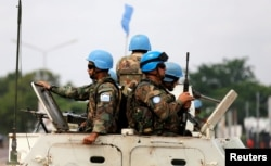 FILE - Peacekeepers serving in the United Nations Organization Stabilization Mission in the Democratic Republic of the Congo (MONUSCO) patrol in their armoured personnel carrier during demonstrations against Congolese President Joseph Kabila in the street
