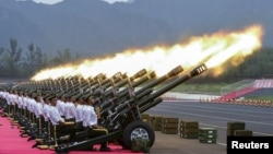 FILE - Paramilitary policemen and members of a gun salute team fire cannons during a training session for a military parade to mark the 70th anniversary of the end of the World War Two, at a military base in Beijing, China. China is now the world's third largest arms exporter behind the U.S. and Russia, and the country accounted for nearly six percent of arms exports between 2011 and 2015.