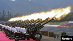 Paramilitary policemen and members of a gun salute team fire cannons during a training session for a military parade to mark the 70th anniversary of the end of the World War Two, at a military base in Beijing, China.
