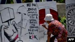 Seorang seniman melukis papan protes dalam unjuk rasa menentang revisi UU KPK di Banda Aceh, 17 September 2019. (Foto: AFP)