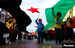 FILE - Children hold up a Syrian Opposition flag during a rally against the government of Syria and Egypt in central Sydney, Sept. 1, 2013.