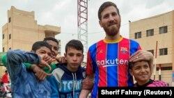 Islam Mohammed Ibrahim Battah, seorang berkebangsaan Mesir yang mirip dengan Lionel Messi, berpose dengan anak laki-laki, di kota Delta Nil Zagazig, utara Kairo, Mesir 23 Maret 2021. (Foto: REUTERS/Sherif Fahmy)