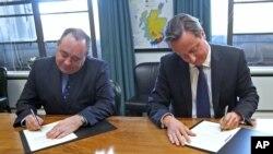PM Inggris David Cameron (kanan) dan Kepala Pemerintahan Skotlandia Alex Salmond menandatangani kesepakatan bagi referendum di Edinburgh, hari Senin (15/10).