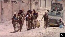 Esta imagen tomada de un video divulgado el martes, 4 de julio de 2017, suministardo por Furat FM, un grupo activista sirio kurdo, muestra a combatientes de las Fuerzas Democráticas Sirias, respaldadas por EE.UU. en el este de Raqqa, Siria.