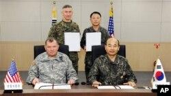 Ketua Dewan Kepala Staf Angkatan Bersenjata Korea Selatan Jung Seun-jo (kanan) dan panglima pasukan Amerika di Korea Selatan, Jenderal James Thurman berpose seusai penandatanganan kesepakatan militer si Seoul, Korea Selatan (22/3).