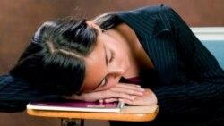 A teenager sleeps at a school desk