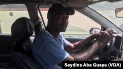 Modou Fall au volant de sa voiture, à Dakar, le 9 décembre 2019. (VOA/Seydina Aba Gueye)