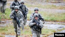 FILE - U.S. Army soldiers train during an exercise at the Adazi Training Area, Latvia, Oct. 20, 2010. The U.S. is deploying troops to Poland, the Baltic states and Romania as part of efforts to bolster regional security, officials say.