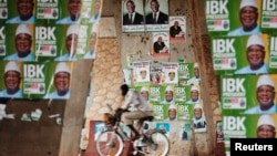 A man rides a bicycle past electoral campaign posters in Bamako August 9, 2013.