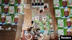 Seorang pengendara sepeda melintasi poster-poster dua kandidat presiden Mali di Bamako (9/8).
