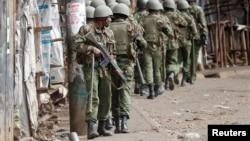 ຕຳຫຼວດ ເຄັນຢາພວມຍ່າງ ໃນລະຫວ່າງການປະທະກັນ ກັບພວກສະໜັບສະໜູນຜູ້ນຳພັກຝ່າຍຄ້ານ ທ່ານ Raila Odinga, ໃນເຂດຊຸມຊົນແອອັດ Kibera, ນະຄອນຫຼວງ ໄນໂຣບີ, ເຄັນຢາ. 12 ສິງຫາ, 2017.